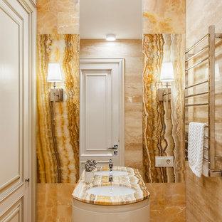 На фото: ванная комната в стиле неоклассика (современная классика) с белыми фасадами, желтой плиткой, плиткой из листового камня, врезной раковиной, столешницей из оникса, бежевым полом, бежевой столешницей и полом из травертина с