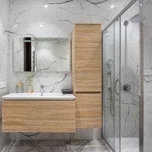 Стильный дизайн: ванная комната в современном стиле с плоскими фасадами, светлыми деревянными фасадами, душем в нише, белой плиткой, консольной раковиной, серым полом и душем с раздвижными дверями - последний тренд