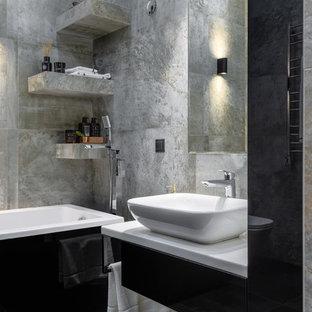 Свежая идея для дизайна: главная ванная комната среднего размера в современном стиле с черными фасадами, инсталляцией, серой плиткой, керамогранитной плиткой, серыми стенами, полом из керамогранита, столешницей из искусственного камня, белой столешницей, плоскими фасадами, настольной раковиной и серым полом - отличное фото интерьера