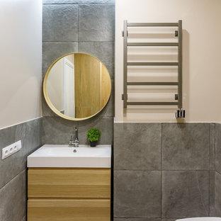Пример оригинального дизайна: ванная комната в современном стиле с плоскими фасадами, светлыми деревянными фасадами, серой плиткой, бежевыми стенами, монолитной раковиной и серым полом