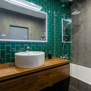 Design ideas for an industrial bathroom in Moscow with flat-panel cabinets, medium wood cabinets, an alcove tub, a shower/bathtub combo, green tile, a vessel sink and wood benchtops.