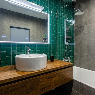 Diseño de cuarto de baño urbano con armarios con paneles lisos, puertas de armario de madera oscura, bañera empotrada, combinación de ducha y bañera, baldosas y/o azulejos verdes, lavabo sobreencimera y encimera de madera