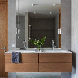 Стильный дизайн: главная ванная комната в современном стиле с плоскими фасадами, фасадами цвета дерева среднего тона, серой плиткой, серым полом, серыми стенами и монолитной раковиной - последний тренд