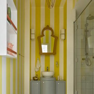 На фото: ванная комната среднего размера в современном стиле с серыми фасадами, душем в нише, керамогранитной плиткой, желтыми стенами, полом из керамогранита, душевой кабиной, бежевым полом, душем с распашными дверями, плоскими фасадами и настольной раковиной с