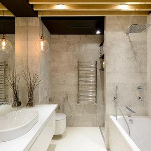Новый формат декора квартиры: маленькая главная ванная комната в стиле лофт с плоскими фасадами, белыми фасадами, ванной в нише, комбинацией ванны с душем, настенным унитазом, белой плиткой, керамогранитной плиткой, серыми стенами, накладной раковиной, столешницей из искусственного камня и белым полом