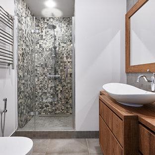 Идея дизайна: ванная комната в современном стиле с плоскими фасадами, фасадами цвета дерева среднего тона, душем в нише, серой плиткой, белыми стенами, душевой кабиной, настольной раковиной, столешницей из дерева, серым полом, душем с распашными дверями и коричневой столешницей