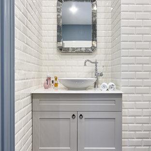 На фото: ванная комната в стиле неоклассика (современная классика) с серыми фасадами, белой плиткой, керамической плиткой, синими стенами, настольной раковиной, черным полом, белой столешницей и фасадами с утопленной филенкой с