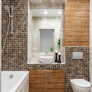 На фото: главная ванная комната в современном стиле с плоскими фасадами, фасадами цвета дерева среднего тона, инсталляцией, плиткой мозаикой, настольной раковиной, белой столешницей, бежевым полом, полновстраиваемой ванной, бежевой плиткой и столешницей из плитки