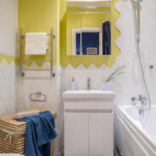 Kleines Modernes Badezimmer En Suite mit flächenbündigen Schrankfronten, weißen Schränken, Badewanne in Nische, Duschbadewanne, weißen Fliesen, gelber Wandfarbe, integriertem Waschbecken, grauem Boden und Duschvorhang-Duschabtrennung in Moskau