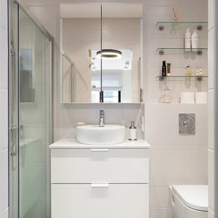 На фото: маленькая ванная комната в современном стиле с плоскими фасадами, белыми фасадами, инсталляцией, белой плиткой, керамической плиткой, полом из керамогранита, душевой кабиной, столешницей из искусственного камня, серым полом, душем с раздвижными дверями, белой столешницей, душем в нише и настольной раковиной с