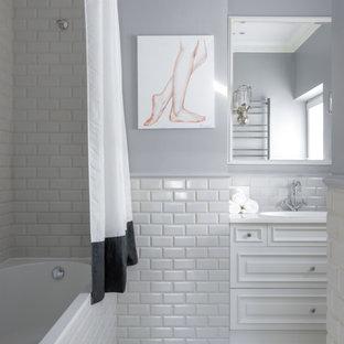 На фото: главная ванная комната в классическом стиле с фасадами с выступающей филенкой, белыми фасадами, ванной в нише, душем над ванной, белой плиткой, плиткой кабанчик, шторкой для ванной, белой столешницей, серыми стенами, монолитной раковиной, полом из керамогранита и белым полом