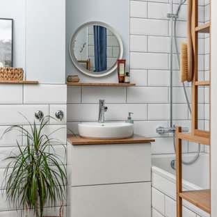 This is an example of a scandinavian ensuite bathroom in Other with flat-panel cabinets, white cabinets, an alcove bath, a shower/bath combination, white tiles, metro tiles, grey walls, wood-effect flooring, a vessel sink, brown floors, a shower curtain, brown worktops, a single sink and a floating vanity unit.