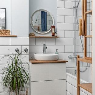 他の地域の北欧スタイルのおしゃれなマスターバスルーム (フラットパネル扉のキャビネット、白いキャビネット、アルコーブ型浴槽、シャワー付き浴槽、白いタイル、サブウェイタイル、グレーの壁、木目調タイルの床、ベッセル式洗面器、茶色い床、シャワーカーテン、ブラウンの洗面カウンター、洗面台1つ、フローティング洗面台) の写真