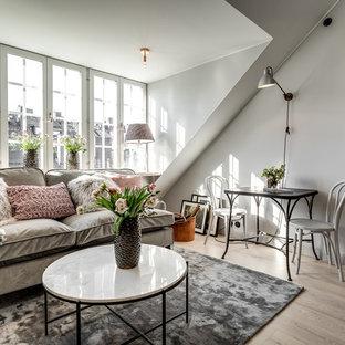 Inredning av ett nordiskt allrum med öppen planlösning, med grå väggar, ljust trägolv och beiget golv
