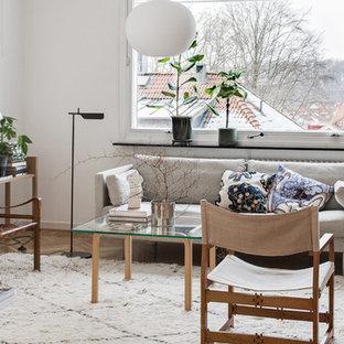 Inspiration för ett skandinaviskt allrum med öppen planlösning, med vita väggar och ljust trägolv