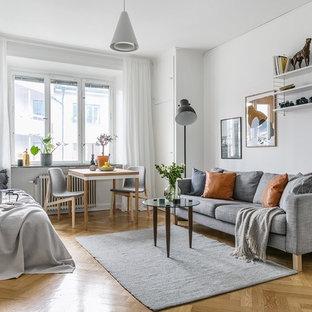 Inspiration för ett litet nordiskt allrum med öppen planlösning, med vita väggar, mellanmörkt trägolv, ett finrum och beiget golv