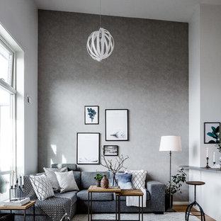 Ejemplo de salón para visitas abierto, nórdico, de tamaño medio, sin televisor, con paredes grises y suelo de madera clara