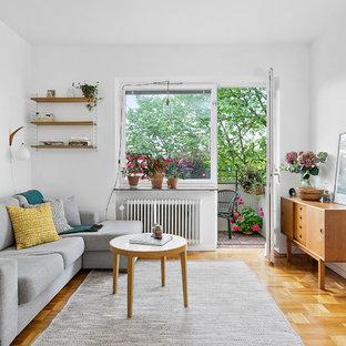 Exempel på ett minimalistiskt allrum med öppen planlösning, med vita väggar, mellanmörkt trägolv och brunt golv