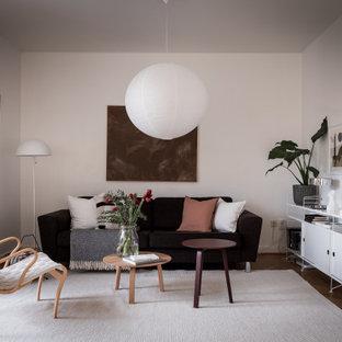 Inspiration för mellanstora skandinaviska vardagsrum, med vita väggar, mellanmörkt trägolv och brunt golv