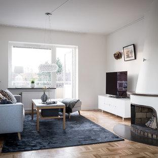 Idéer för minimalistiska separata vardagsrum, med vita väggar, mellanmörkt trägolv, en standard öppen spis, en spiselkrans i gips, en fristående TV och brunt golv