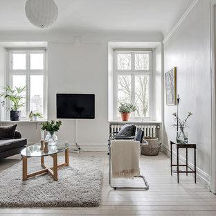 Exempel på ett stort nordiskt separat vardagsrum, med vita väggar, en väggmonterad TV, vitt golv och ljust trägolv