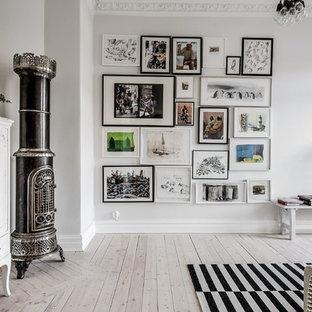 Bild på ett nordiskt vardagsrum, med vita väggar, ljust trägolv, en öppen vedspis, en spiselkrans i metall och beiget golv
