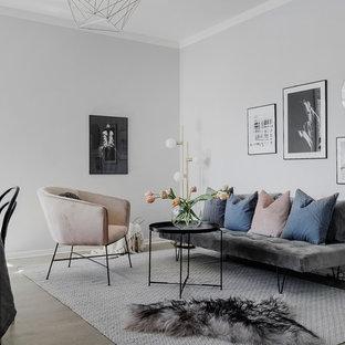 Idéer för att renovera ett litet minimalistiskt allrum med öppen planlösning, med ljust trägolv och grå väggar