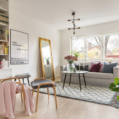 Example of a large danish formal and enclosed light wood floor living room design in Stockholm with white walls and no tv