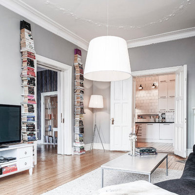 Example of a large danish formal and open concept light wood floor living room design in Gothenburg with gray walls and a tv stand