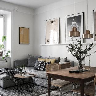 Foto på ett minimalistiskt allrum med öppen planlösning, med grå väggar och grått golv
