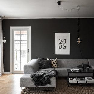 Idee per un piccolo soggiorno scandinavo chiuso con pareti nere, parquet chiaro e pavimento beige