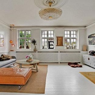Immagine di un grande soggiorno nordico chiuso con pareti bianche, pavimento in legno verniciato, camino classico, TV a parete, sala formale e cornice del camino in pietra
