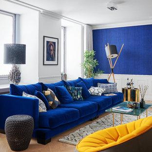 Modern inredning av ett mellanstort allrum med öppen planlösning, med ett finrum, blå väggar, ljust trägolv och beiget golv