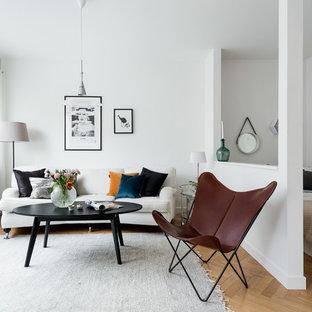 Skandinavisk inredning av ett litet allrum med öppen planlösning, med vita väggar och mellanmörkt trägolv