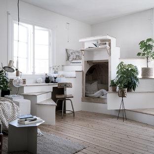 Inredning av ett skandinaviskt litet allrum med öppen planlösning, med vita väggar, ljust trägolv och ett finrum