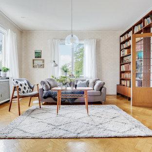 Idéer för ett skandinaviskt separat vardagsrum, med ett bibliotek, beige väggar, mellanmörkt trägolv och brunt golv