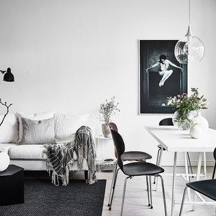 Exempel på ett minimalistiskt vardagsrum, med vita väggar och ljust trägolv
