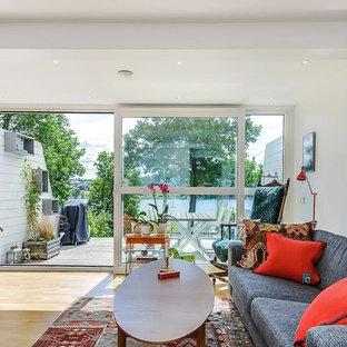 Imagen de salón para visitas abierto, ecléctico, grande, sin chimenea, con paredes blancas, suelo de madera clara y televisor independiente