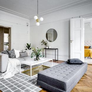 Skandinavisk inredning av ett mycket stort separat vardagsrum, med vita väggar och ljust trägolv