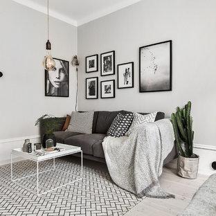 Imagen de salón para visitas cerrado, escandinavo, de tamaño medio, sin chimenea, con paredes grises y suelo de madera clara