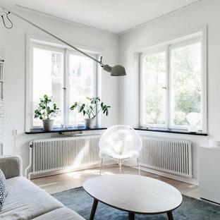 Imagen de salón para visitas nórdico, de tamaño medio, con paredes blancas, suelo de madera clara y televisor colgado en la pared