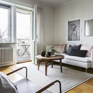 Bild på ett nordiskt vardagsrum, med vita väggar, ljust trägolv och beiget golv