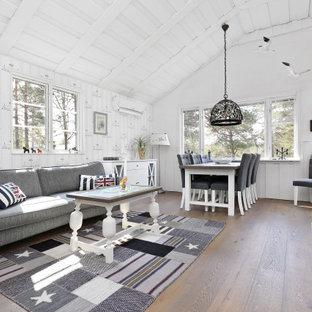 Idéer för minimalistiska allrum med öppen planlösning, med vita väggar, mellanmörkt trägolv, en fristående TV och brunt golv