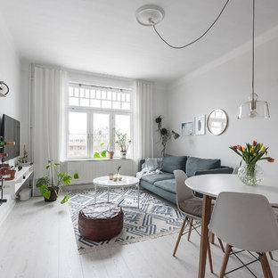 Bild på ett mellanstort nordiskt vardagsrum, med vita väggar, laminatgolv och vitt golv