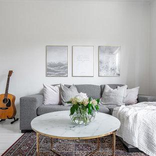 Minimalistisk inredning av ett mellanstort vardagsrum, med vita väggar, målat trägolv och vitt golv