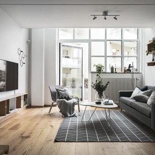Nordisk inredning av ett vardagsrum, med vita väggar, en väggmonterad TV och brunt golv