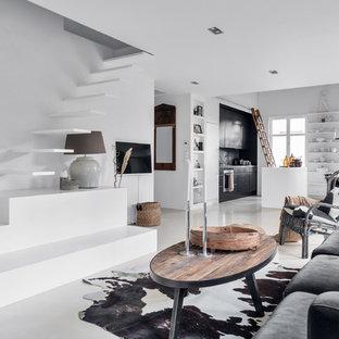 Inredning av ett modernt allrum med öppen planlösning, med vita väggar, betonggolv, en väggmonterad TV och vitt golv