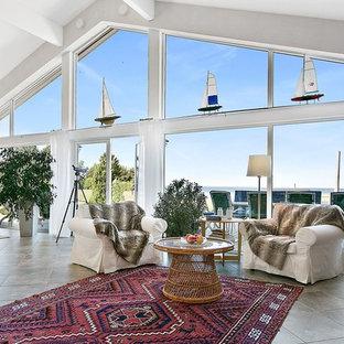 ヨーテボリの中サイズのビーチスタイルのおしゃれなLDK (白い壁、フォーマル、ライムストーンの床、薪ストーブ、内蔵型テレビ) の写真