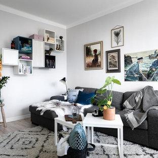 Inspiration för små minimalistiska vardagsrum, med vita väggar, ljust trägolv och beiget golv