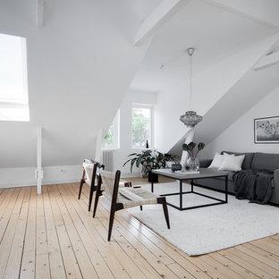 Foto på ett mellanstort nordiskt loftrum, med vita väggar, ljust trägolv, beiget golv och ett finrum